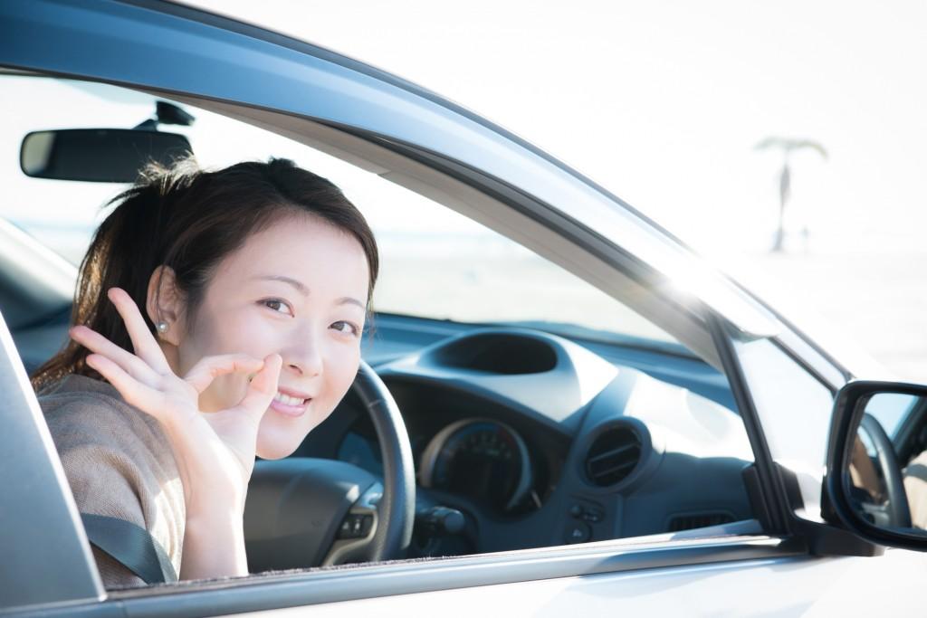 笑顔で車に乗る女性