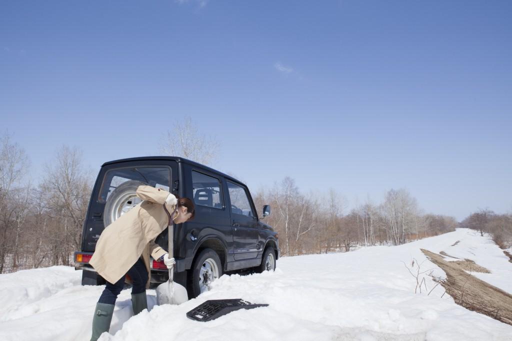 スコップで雪を固める女性