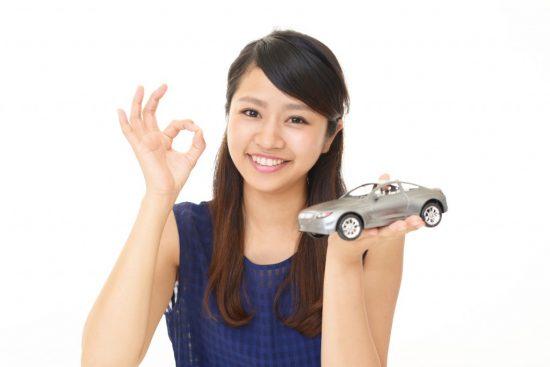 車の模型を片手にOKサインを出す女性