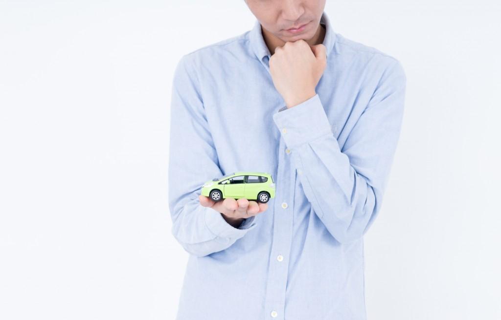 買う車を悩む男性
