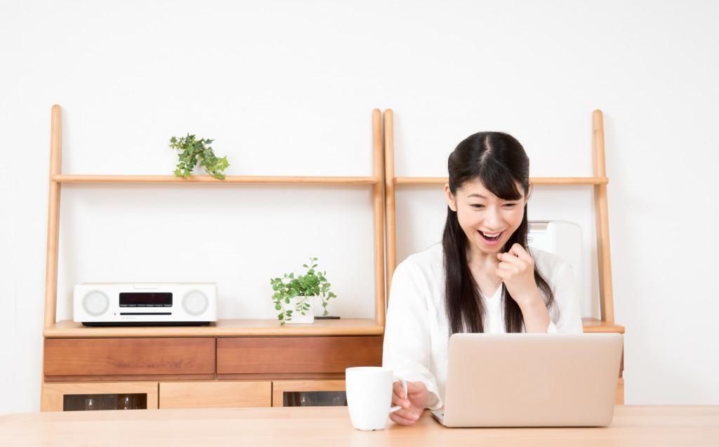 パソコンの画面を見て驚く女性