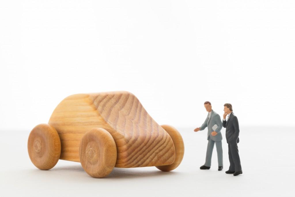 車を見ながら相談する男性