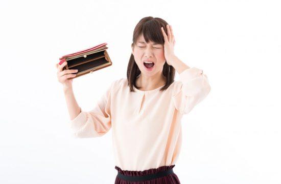 空っぽの財布に頭を抱える女性