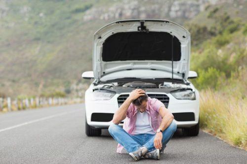 車が故障して困り果てる男性