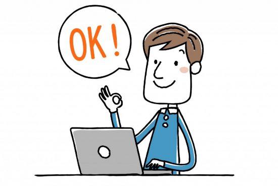 パソコンの前でOKサインを出す男性